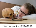 Woman examining a human skull - stock photo