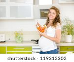 Pregnant woman in kitchen eating a salad smiling.looking at camera - stock photo