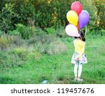 Outdoor portrait of little girl holding bunch of balloons - stock photo