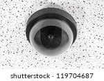 Overhead security camera globe on acoustic tile. - stock photo