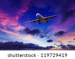 Plane in a sunset sky - stock photo