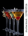 Classical martini in chilled glass over black background on reflection surface, garnished with freah blackberry, maraschino cherry, marinated peaMost popular cocktails series. - stock photo