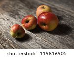 Organic apples on a rustic wooden board - stock photo