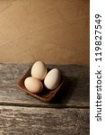 Free range chicken eggs in a wooden bowl on a rustic wooden board - stock photo