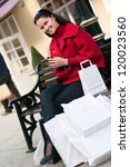 Happy smiling woman sitting on the bench after shopping - stock photo