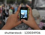BANGKOK - NOV 24: A protesters uses a smartphone to video an anti-government Pitak Siam rally at Makhawan Bridge on Nov 24, 2012 in Bangkok, Thailand. - stock photo