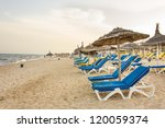 Hammamet beach with shades made of straw, blue beach chairs and beautiful white sand along the coast of the Mediterranean sea - stock photo