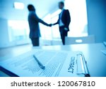 Image of business contract on background of two employees handshaking - stock photo