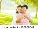 Asian senior mother and adult daughter at outdoor park - stock photo
