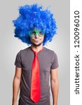 funny guy with blue wig green eyeglasses and red tie on grey background - stock photo