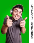 funny guy listening to music on green background - stock photo
