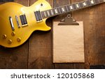 Vintage gold top single cutaway guitar on old wood surface and old clipboard, good for playlists, and production notes. - stock photo