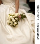 bride holding white rose bouquet shot with tilt-shift lens - stock photo