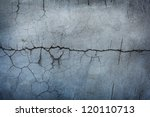 Grungy stone wall with big crack running across the middle. - stock photo