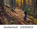 Stock photo a girl walking her dog in colorful autumn forest in the mountains 120203623