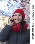 the young girl in a red knitted cap and a red scarf speaks by phone on the winter street - stock photo