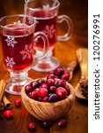 Cranberries in wooden bowl with hot mulled wine - stock photo
