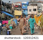 MUMBAI, INDIA-NOV.27: Women in district of slums on Nov. 27,2010 in Mumbai.Growth in urban population has resulted in a large section of  population living in abject poverty in overcrowded slums. - stock photo