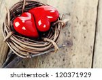 Two red hearts in bird's nest on wooden board- yin-yang and Valentine concept - stock photo
