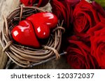 Two red hearts in bird's nest  and roses on wooden board - stock photo