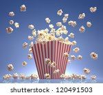 Popcorn exploding inside the packaging striped. - stock photo