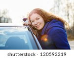 Young pretty woman standing near car against sun lights - stock photo