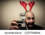 christmas bearded man holding old camera on grey background - stock photo