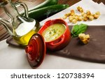 Cream of zucchini in a little casserole with croutons, oil and fresh vegetables - stock photo