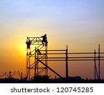 Construction workers high up on a scaffold seen against the setting sun - stock photo