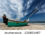 Small photo of Turquoise and white Portuguese moliceiros fishing boat, oar reaching to sky, resting on sandy beach facing the ocean waves in the Beria Litoral