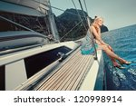 cheerful young blond girl sitting on a luxury yacht - stock photo