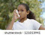 Portrait of a girl using asthma inhaler - stock photo
