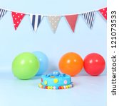 Kids blue round birthday party cake with red, yellow, blue and pink polka dots and cute blue fondant octopus on top. All on blue background with balloons and flag bunting. - stock photo
