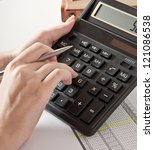 Woman's hand with a pen, calculator and the financial report - stock photo
