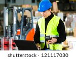 Warehouseman with protective vest, scanner and laptop in warehouse at freight forwarding company - stock photo