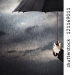Human hands holding big black umbrella under the heavy rain - stock photo