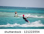 Kiteboarders enjoy surfing in blue water - stock photo