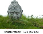 Stone Buddha decoration bust in garden grass - stock photo