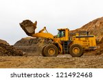 Yellow bulldozer in quarry - stock photo