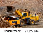 Bulldozer loading ground in truck - stock photo