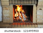 Fireplace with wood and fire closeup - stock photo
