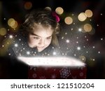 Child opening a magic gift box with lights and shining around - stock photo