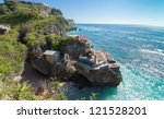 Ulu Watu coastline with beaautiful rocky cliffs and turquoise wavey sea. - stock photo