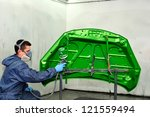Spraying a green bonnet. - stock photo