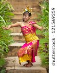 Young Balinese female dancer performing traditional Legong dance - stock photo
