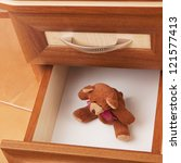 teddy bear in open desk  drawer in a modern office - stock photo