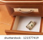roll of United States dollars in open desk  drawer - stock photo