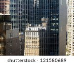 Old style metal water towers on stilts on top of a brownstone reflected in a new glass and steel skyscraper in new york city - stock photo
