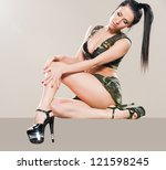 Sexy stripper in camouflage posing in studio - stock photo
