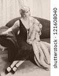 Fancy lady in 1920s style sitting on a luxury chaise-longue - noise has been added for vintage effect - stock photo